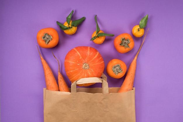 Frutas e vegetais laranja em saco de papel artesanal no fundo violeta.