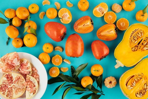 Frutas e vegetais maduros e saborosos de laranja em fundo azul, incluindo tangerinas, abóbora, granato e caqui