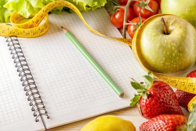 Frutas e vegetais orgânicos frescos, abra o caderno em branco e uma caneta sobre fundo de madeira. alimentação saudável e conceito de vida saudável.