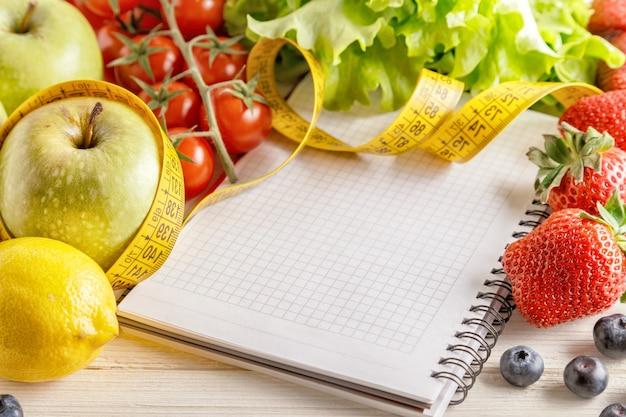 Frutas e vegetais orgânicos frescos, caderno em branco aberto e caneta na madeira