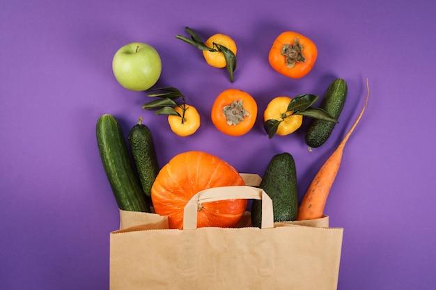 Frutas e vegetais verdes e laranja no saco de papel artesanal no fundo violeta.