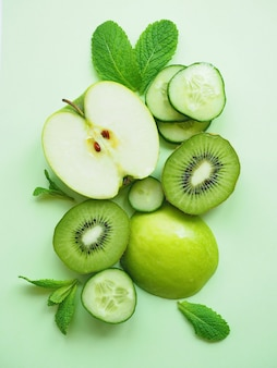 Frutas e vegetais verdes maçã kiwi pepino folhas de hortelã na superfície verde