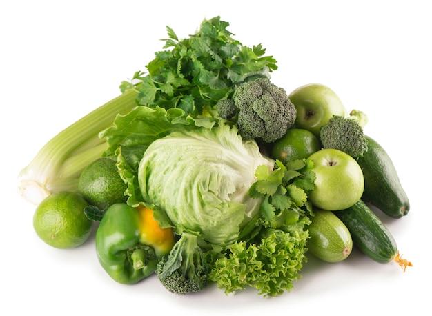 Frutas e vegetais verdes na superfície branca.