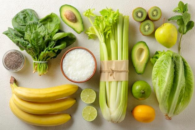 Frutas e vegetais verdes são os ingredientes de uma bebida desintoxicante. espinafre, abacate, aipo e vários.