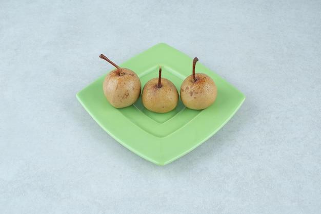 Frutas em conserva caseiras na placa verde.