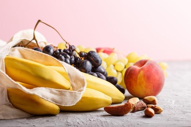 Frutas em saco reutilizável de tecido branco de algodão em uma parede cinza e rosa. zero resíduos compras, armazenamento e reciclagem conceito. vista lateral, close-up, copie o espaço.