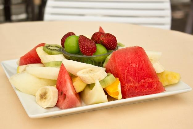 Frutas em um prato. ameixa verde, morango, banana, kiwi, melancia, laranja e maçã.