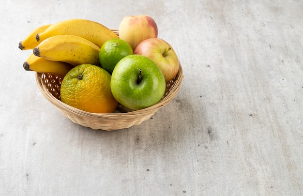 Frutas em uma cesta sobre a mesa com espaço de cópia.