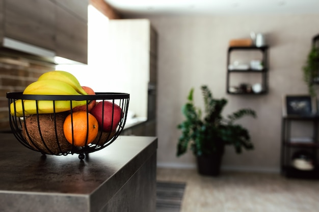 Frutas em uma fruteira no balcão do bar na elegante cozinha loft.