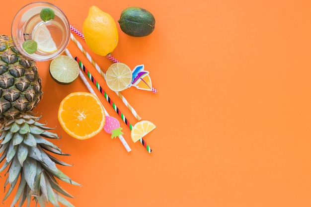 Frutas exóticas com coquetel e canudos de plástico