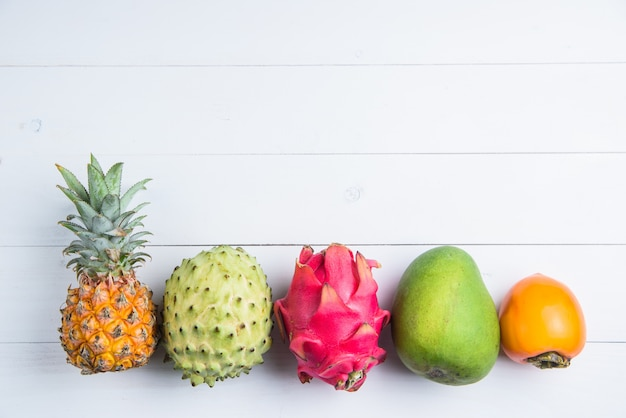 Frutas exóticas de verão fresco em branco. fruta do dragão, abacaxi, caqui, manga, annona cherimola plana leigos com espaço de cópia gratuita.