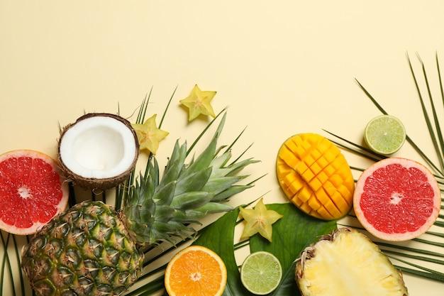 Frutas exóticas e folhas de palmeira em fundo bege, espaço para texto