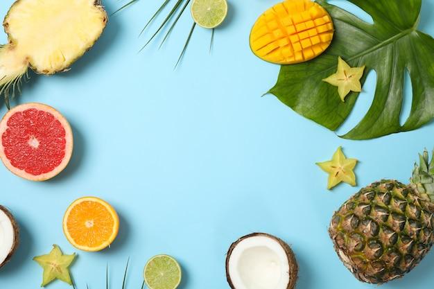 Frutas exóticas e folhas de palmeira sobre fundo azul, espaço para texto