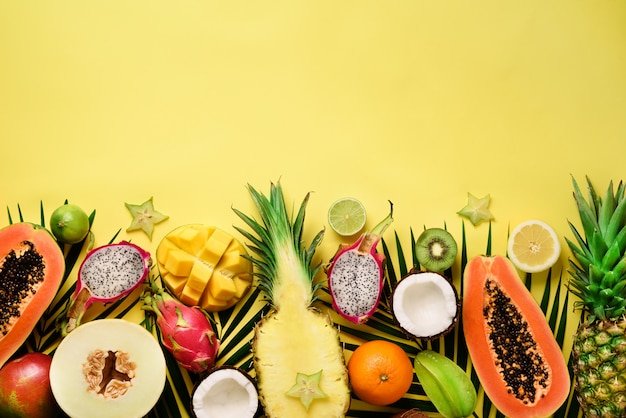 Frutas exóticas e folhas de palmeira tropicais - mamão, manga, abacaxi, banana, carambola, fruta do dragão, kiwi, limão, laranja, melão, coco, limão.