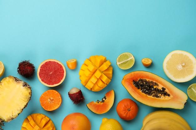 Frutas exóticas em fundo azul, espaço para texto.