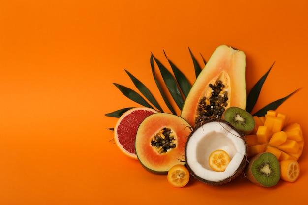 Frutas exóticas em fundo laranja, espaço para texto.
