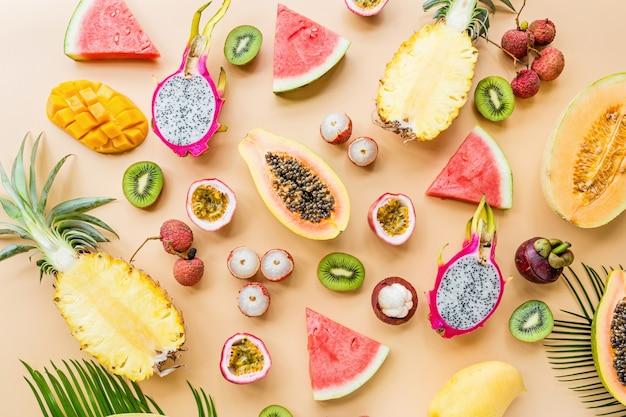 Frutas exóticas frescas e palmeira tropical deixa no fundo laranja pastel