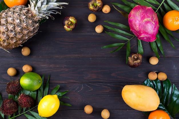 Frutas exóticas frescas em uma caixa de madeira, vista superior com muitos frutos maduros coloridos