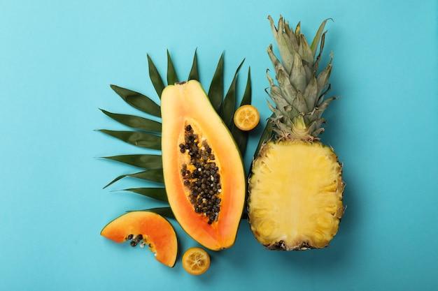 Frutas exóticas frescas maduras sobre fundo azul.