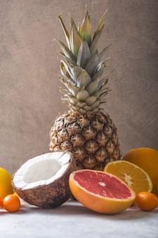 Frutas exóticas frescas no cinza pastel - abacaxi, toranja, coco, laranja. maquete, configuração plana, sobrecarga. vista do topo.