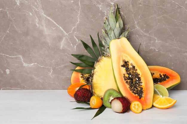 Frutas exóticas maduras contra um plano de fundo texturizado cinza.