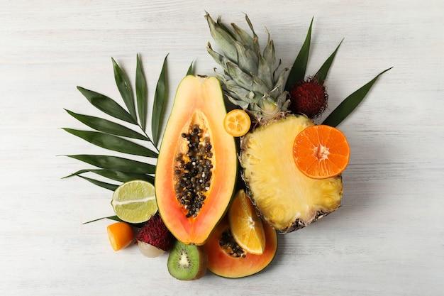 Frutas exóticas maduras em fundo branco de madeira.