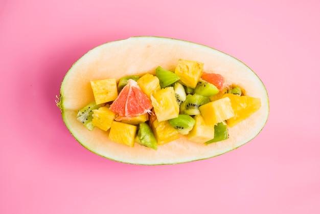 Frutas fatiadas com metade de melão no fundo rosa