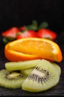 Frutas fatiadas (morangos, kiwi, laranja, banana) sobre um fundo preto
