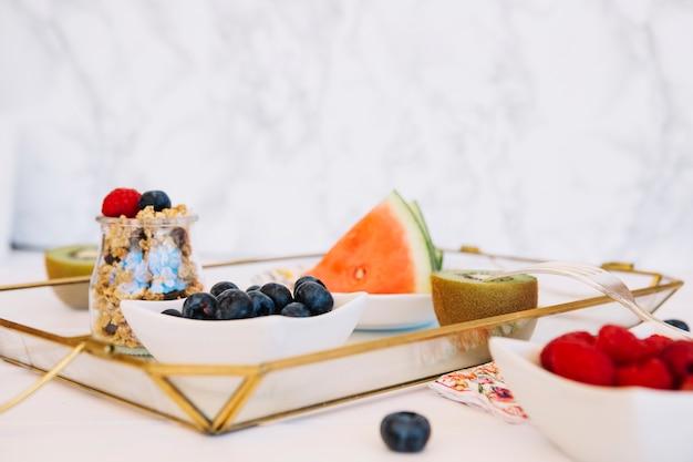 Frutas frescas; aveia e mirtilos na bandeja