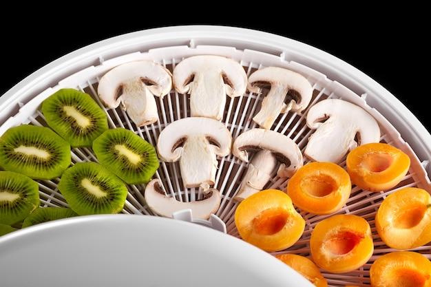 Frutas frescas, bagas e cogumelos fatiados em fatias em uma bandeja para secar ou congelar