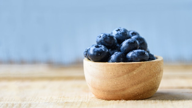Frutas frescas blueberries na tigela sobre a mesa de madeira azul