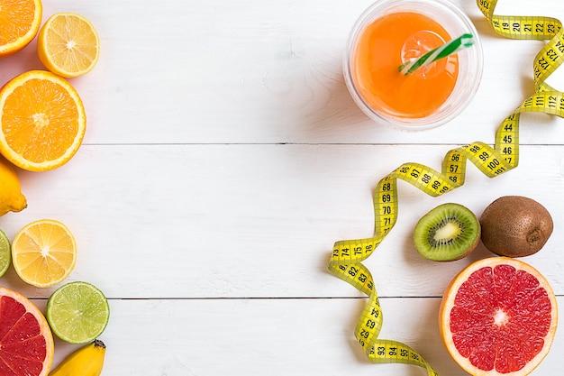 Frutas frescas com fita métrica sobre fundo branco de madeira vista superior