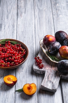 Frutas frescas de ameixa doce inteiras e fatiadas em um prato com folhas de alecrim em uma velha tábua de corte com bagas de groselha em uma tigela de madeira