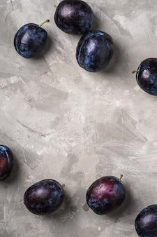 Frutas frescas de ameixa madura com gotas de água na mesa de pedra de concreto, espaço para cópia com vista superior