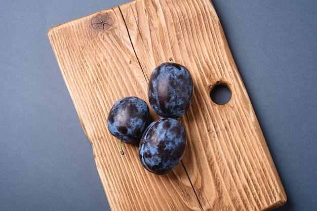 Frutas frescas de ameixa madura em uma tábua de madeira na superfície mínima azul cinza