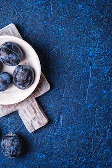 Frutas frescas de ameixa madura em uma tigela de madeira branca e uma velha tábua de corte na mesa abstrata azul, espaço de cópia da vista superior