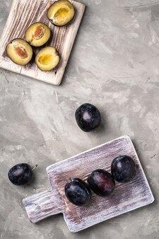 Frutas frescas de ameixa madura inteiras e fatiadas em tábuas de madeira