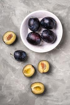 Frutas frescas de ameixa madura inteiras e fatiadas em uma tigela de madeira, mesa de concreto de pedra, vista de cima