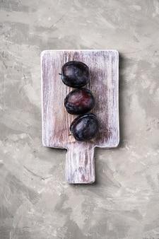 Frutas frescas de ameixa madura na tábua de madeira