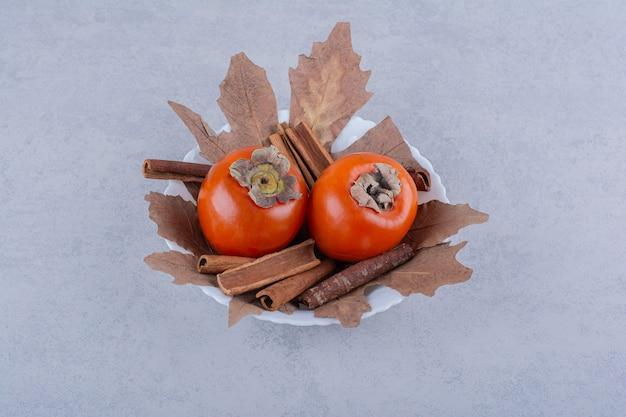 Frutas frescas de caqui com folhas secas em uma tigela branca.
