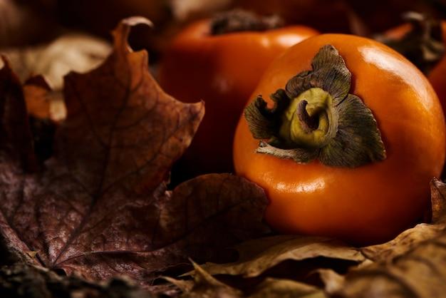 Frutas frescas de caqui em folhas de outono laranja em uma superfície de madeira