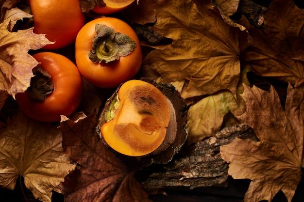 Frutas frescas de caqui fatiado em folhas de outono laranja em uma superfície de madeira