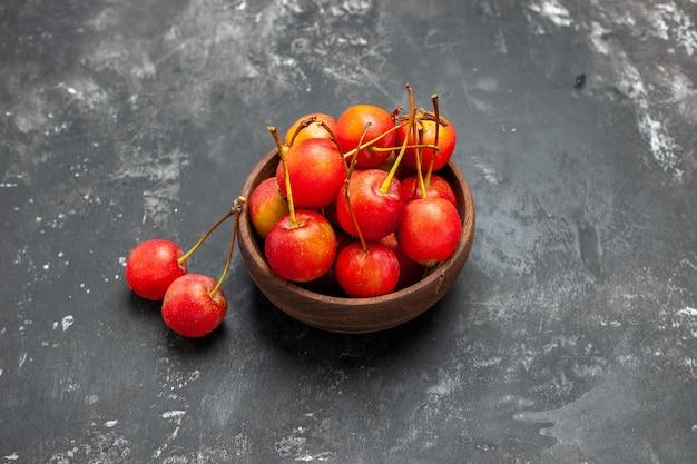 Frutas frescas de cereja vermelha em uma tigela marrom sobre fundo cinza