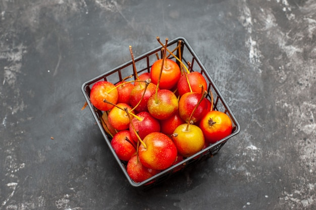 Frutas frescas de cereja vermelha em uma tigela sobre fundo cinza