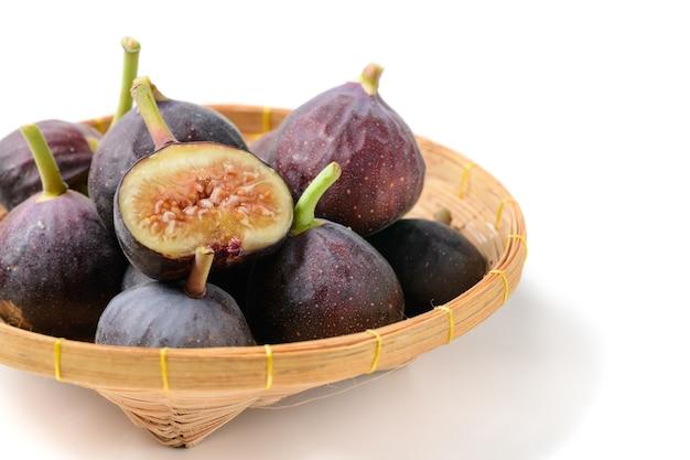 Frutas frescas de figo roxo e fatias em uma cesta de bambu isoladas no fundo branco