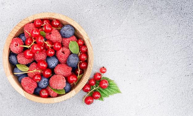 Frutas frescas de framboesa, groselha e mirtilo em um prato sobre um fundo claro de concreto