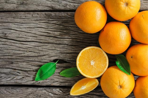Frutas frescas de laranja com folhas na mesa de madeira