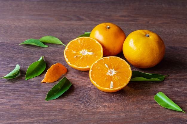 Frutas frescas de laranja e laranja cortadas ao meio em uma mesa de madeira