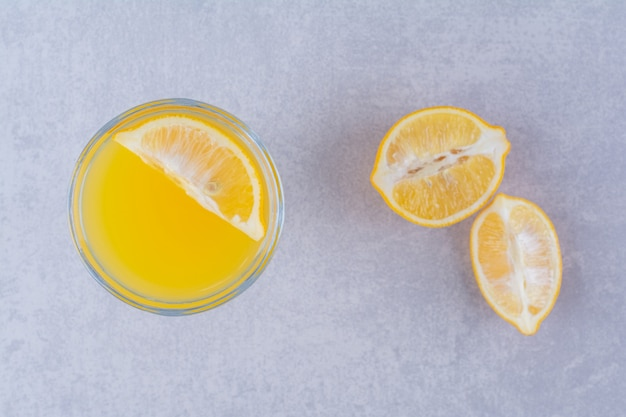 Frutas frescas de laranja e suco na mesa de mármore.
