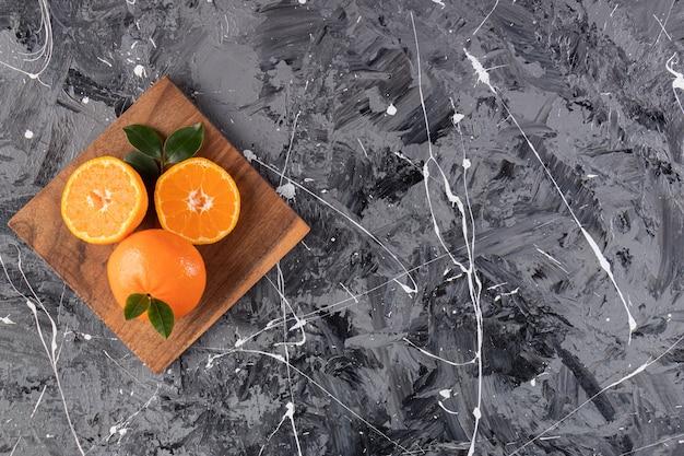 Frutas frescas de laranja em um prato de madeira colocado sobre uma superfície de mármore